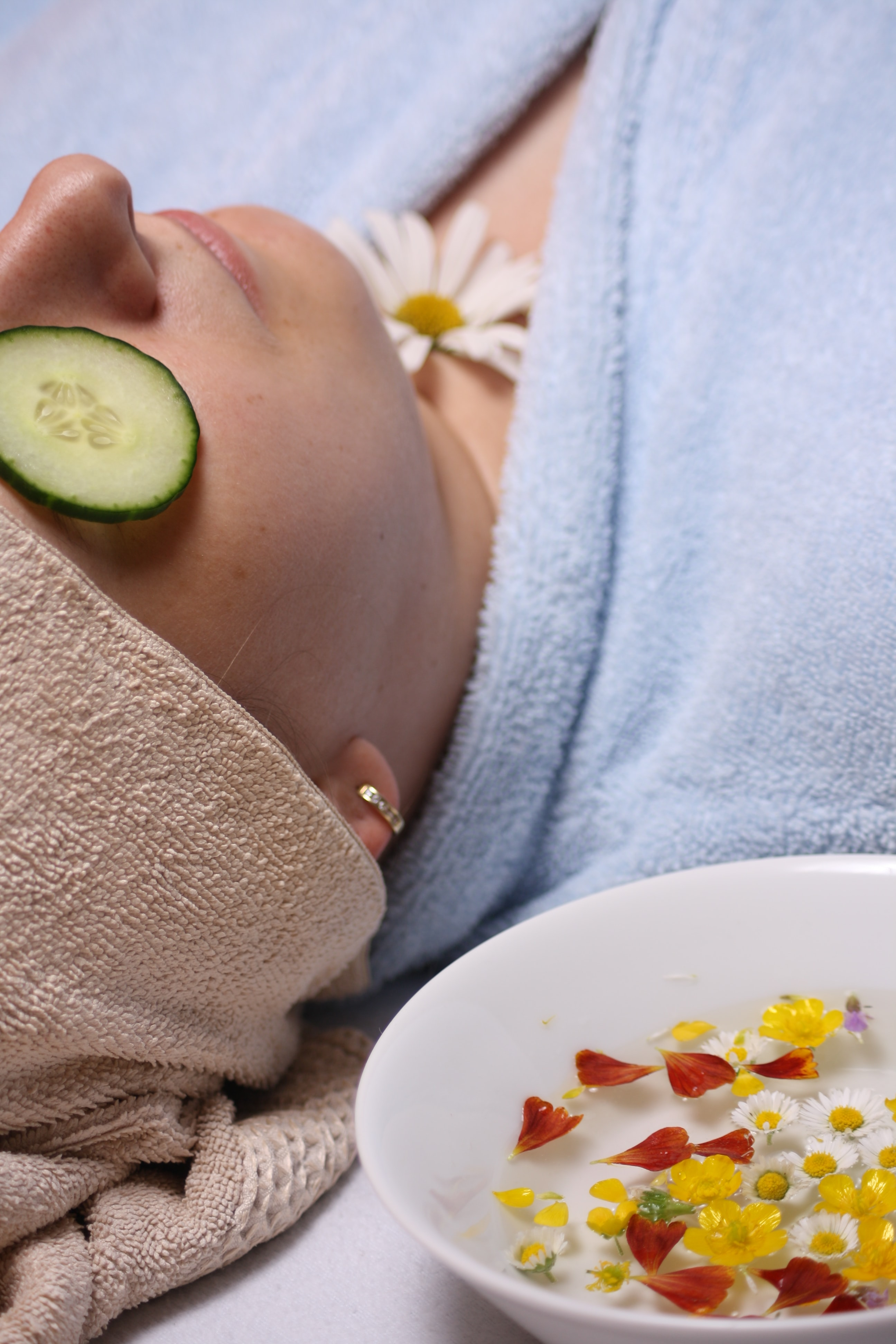 Woman lying with cucumber on eyes