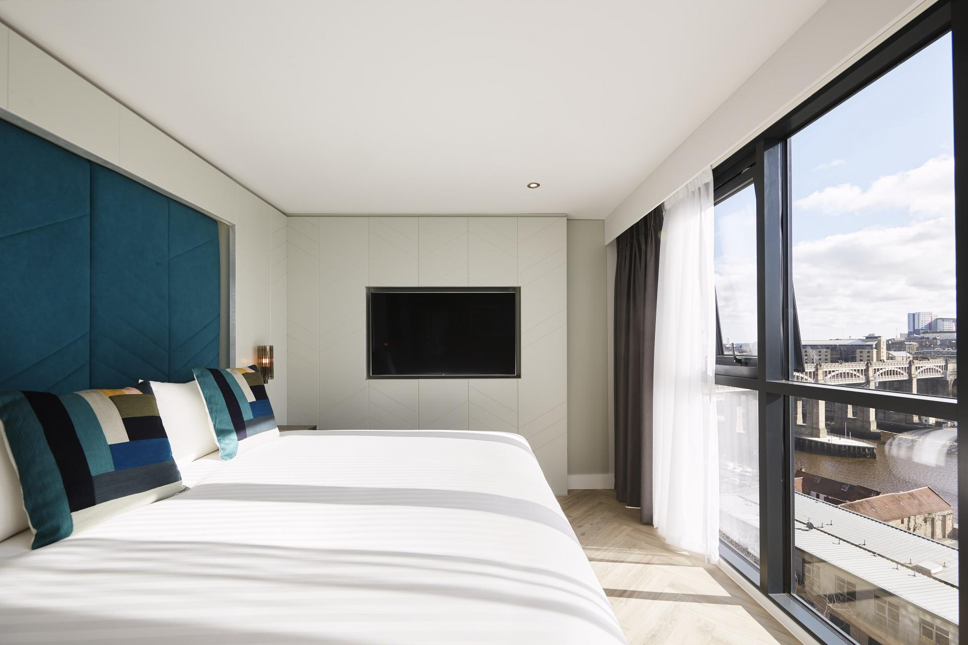 White sheets on a large bed with fantastic views of Newcastle